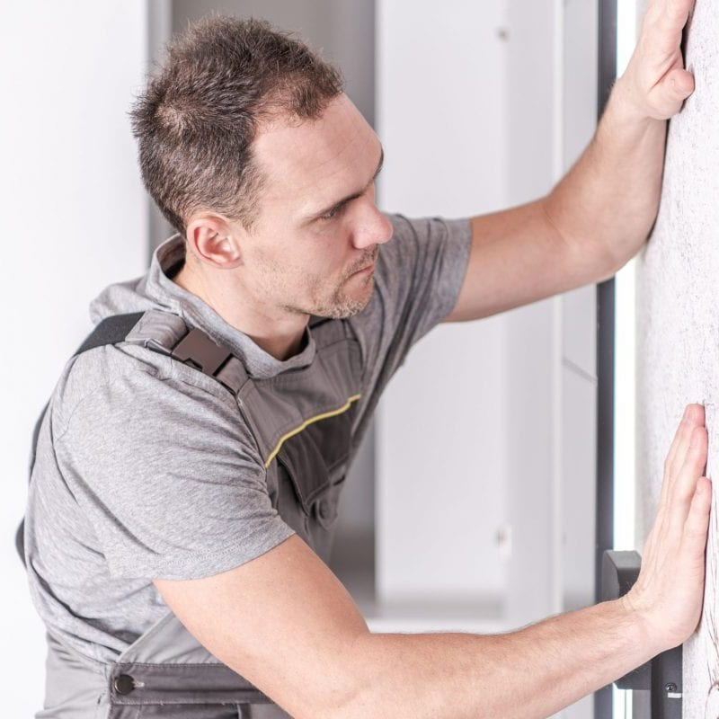 Caucasian Men in His 30s Installing Wallpaper Decoration on His Bedroom's Wall. Modern Home Interior Finishing.